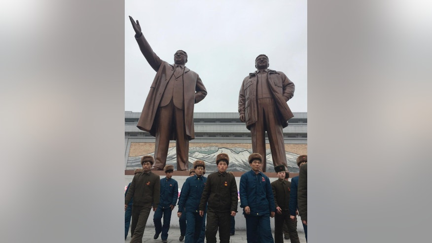 A group of men pay their respects at statues of late North Korean leaders, Kim Il Sung, left, and Kim Jong Il, in Pyongyang, North Korea, Thursday, Feb. 16, 2017. Unaware of reports his eldest son - and current leader Kim Jong Un's half-brother - was killed just days ago in what appears to have been a carefully planned assassination, North Koreans marked Kim Jong Il's birthday on Thursday just as they do every year - with dancing, special treats for the children and treks to city plazas to offer reverential bows and bouquets of flowers before his bronze statues. (AP Photo/Eric Talmadge)