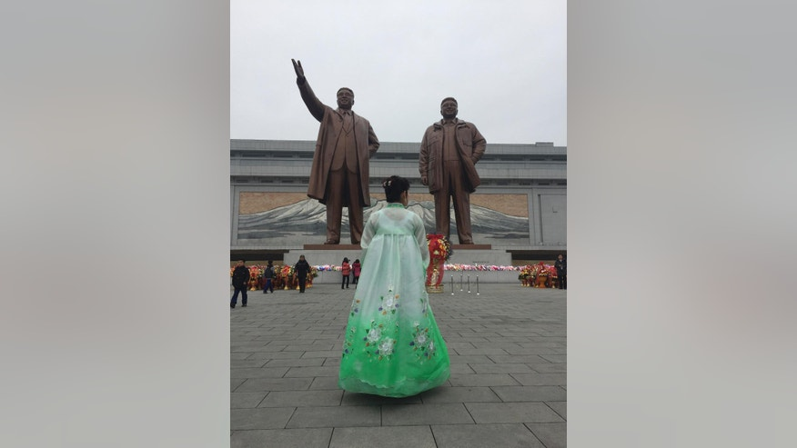 A woman dressed in a traditional gown pays her respects at statues of late North Korean leaders, Kim Il Sung, left, and Kim Jong Il, in Pyongyang, North Korea, Thursday, Feb. 16, 2017. Unaware of reports his eldest son - and current leader Kim Jong Un's half-brother - was killed just days ago in what appears to have been a carefully planned assassination, North Koreans marked the birthday of late leader Kim Jong Il on Thursday as they do every year, with dancing, special treats for the children and treks to city plazas to offer reverential bows and bouquets of flowers before bronze statues.(AP Photo/Eric Talmadge)