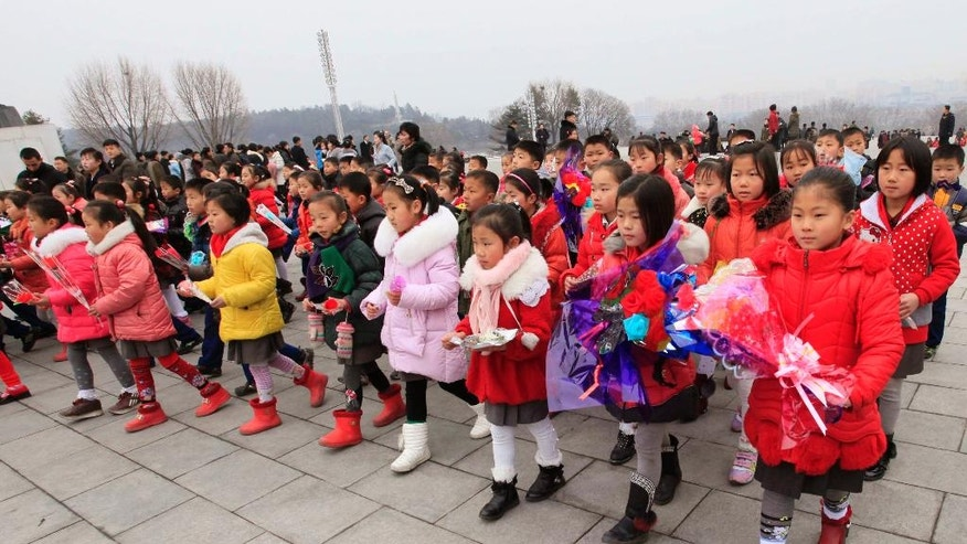 Schoolchildren with offerings walk toward statues of late North Korean leaders Kim Il Sung and Kim Jong Il to pay tribute, in Pyongyang, North Korea, Thursday, Feb. 16, 2017. Unaware of reports his eldest son - and current leader Kim Jong Un's half-brother - was killed just days ago in what appears to have been a carefully planned assassination, North Koreans marked the birthday of late leader Kim Jong Il on Thursday as they do every year, with dancing, special treats for the children and treks to city plazas to offer reverential bows and bouquets of flowers before bronze statues. (AP Photo/Jon Chol Jin)