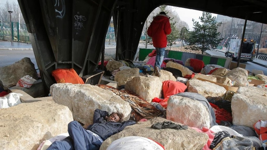A migrant sleeps under a railway bridge in Paris, Thursday, Feb. 16, 2017. Boulders placed under a Paris bridge are causing controversy, as aid groups say they're preventing migrants from setting up camp in an area that has been a magnet for people fleeing war and poverty around the world. (AP Photo/Michel Euler)
