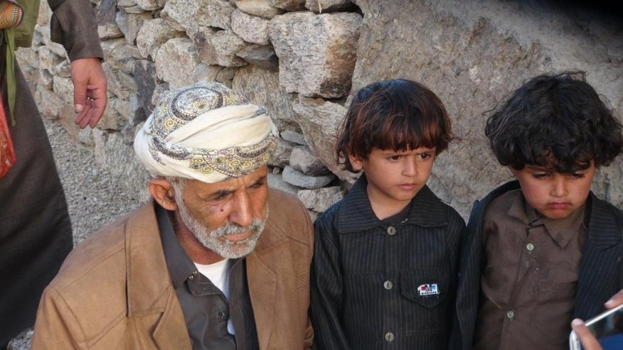 This undated handout photo from the Al-Karama Foundation, a Geneva-based non-governmental human rights organization, shows Abdullah Mabkhout al-Ameri next to a children, after a drone strike in December 2013 that killed his son and eleven others, when it hit a convoy which was allegedly a wedding procession. Al-Ameri and several family members including a son who belonged to al-Qaida were killed in a Jan. 29, 2017, US raid in the village. The raid, which left at least 25 Yemenis dead and a US Navy Seal, showed how difficult it is to tell who is al-Qaida in a country where the militants are mingled with tribes and are fighting on the same side as the government against the rebels. (Farouk al-Sharani, Al-Karama Foundation, via AP)