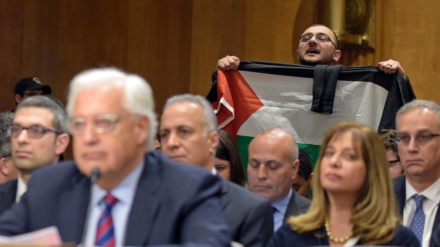 A protestor, holding a Palestinian flag, interrupts David Friedman, nominated to be U.S. Ambassador to Israel, as he testifies on Capitol Hill in Washington, Thursday, Feb. 16, 2017, at his confirmation hearing before the Senate Foreign Relations Committee. (AP Photo/Susan Walsh)
