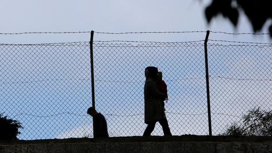 A man with a child, right, and another man, left, walk behind of a fence in the Turkish Cypriot  northern part of Nicosia along the UN buffer zone that divides the Geek and Turkish Cypriots controlled areas in the divided capital of  the eastern Mediterranean island of Cyprus, on Thursday, Feb. 16, 2017. The leader of ethnically divided Cyprus' breakaway Turkish Cypriots has walked out of a meeting with the Greek Cypriot president amid ongoing reunification talks. It's unclear why Mustafa Akinci left Thursday's meeting with Nicos Anastasiades and what this means to the months-long peace process. (AP Photo/Petros Karadjias)