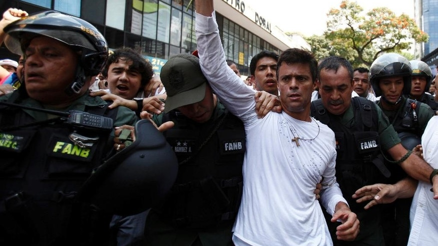 FILE - In this Feb 18, 2014 file photo, opposition leader Leopoldo Lopez, dressed in white and holding up flowers, is taken into custody by Bolivarian National Guards, in Caracas, Venezuela. Venezuela's supreme court rejected an appeal and ratified on Thursday, Feb. 16, 2017, the 14 year sentence given to Lopez. (AP Photo/Alejandro Cegarra, File)