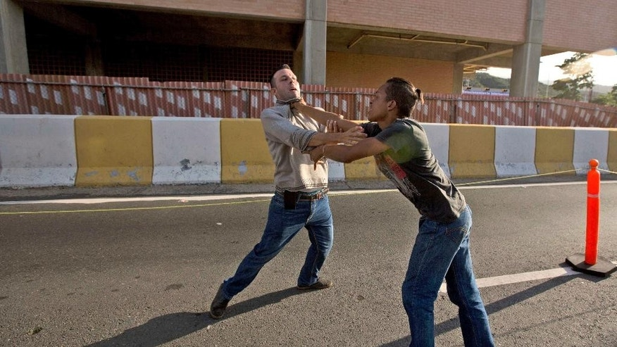 A supporter of Lilian Tintori, wife of jailed opposition leader Leopoldo Lopez, left, and a government supporter clash outside the Simon Bolivar International Airport, in Maiquetia near Caracas, Venezuela, Thursday, Feb. 16, 2017. Tintori was greeted by supporters after returning to Venezuela a day after meeting with U.S. President Donald Trump. The surprise Oval Office meeting Wednesday night between Trump and Tintori sent shockwaves on social media in Venezuela but it remains to be seen if his willingness to quickly take up the cause of the opposition will help or hamper regional efforts to resolve the nation's political and economic crisis. (AP Photo/Fernando Llano)