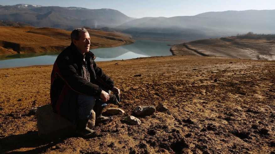 In this photo taken on Thursday, Feb. 16, 2017, Hajrudin Kadric sits on a stone in the drained Ramsko Lake, near the Bosnian town of Rama, 130 kms south of Sarajevo. Kadric never expected to see where his childhood home stood ever again. His home was in one of about 20 villages that were submerged to make an artificial lake nearly a half-century ago to feed a hydroelectric power plant in southern Bosnia, but the lake has been practically drained because of an exceptionally dry and cold winter, which prompted a sharp increase in electricity production. ( AP Photo/Amel Emric)