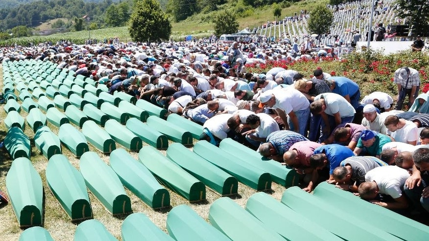 FILE - A  Monday, July 11, 2016 file photo of Bosnian people saying their prayers in front of coffins during a funeral ceremony for the 127 victims at the Potocari memorial complex near Srebrenica, 150 kilometers (94 miles) northeast of Sarajevo, Bosnia and Herzegovina. Twenty one years ago, on July 11, 1995, Serb troops overran the eastern Bosnian Muslim enclave of Srebrenica and executed some 8,000 Muslim men and boys. Bosnia will ask the United Nation's top court to reconsider its 2007 ruling that cleared Serbia of genocide during Bosnia's 1992-95 war.  (AP Photo/Amel Emric, File)