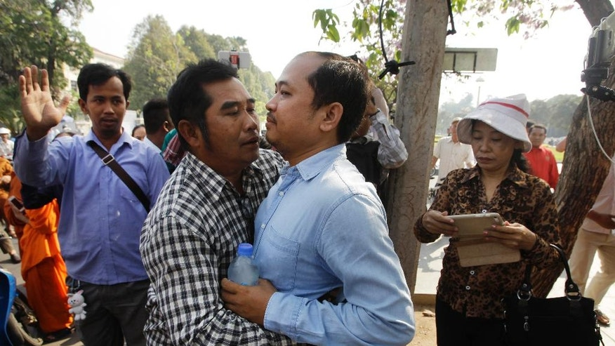 "Political commentator Kim Sok, center right, is hugged by a supporter as he makes his way joined by his supporters to the municipal court in Phnom Penh, Cambodia, Friday, Feb. 17, 2017. Sok joined by 200 supporters walked some five kilometers into the capital to the Phnom Penh Municipal Court answering to the defamation complaint filed by long-serving Prime Minister Hun Sen. Hun Sen filed the lawsuit earlier this week by demanding $500,000 after the commentator blamed his government-affiliated ""network"" for the murder of Cambodia's most prominent political analysis, Kem Ley in July last year. (AP Photo/Heng Sinith)"