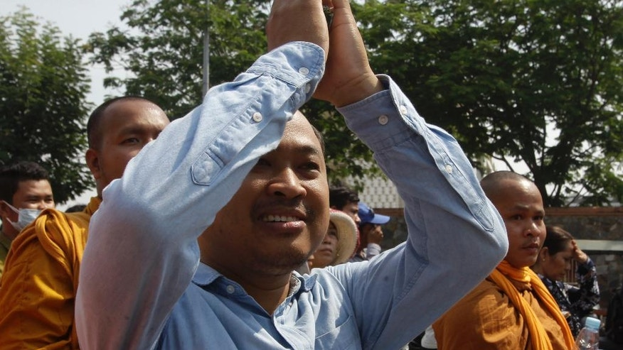 "Political commentator Kim Sok greets his supporters on his way to the municipal court in Phnom Penh, Cambodia, Friday, Feb. 17, 2017. Sok joined by 200 supporters walked some five kilometers into the capital to the Phnom Penh Municipal Court answering to the defamation complaint filed by long-serving Prime Minister Hun Sen. Hun Sen filed the lawsuit earlier this week by demanding $500,000 after the commentator blamed his government-affiliated ""network"" for the murder of Cambodia's most prominent political analysis, Kem Ley in July last year. (AP Photo/Heng Sinith)"