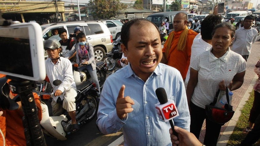 "Political commentator Kim Sok, center, talks to the press as he makes his way joined by his supporters to the municipal court in Phnom Penh, Cambodia, Friday, Feb. 17, 2017. Sok joined by 200 supporters walked some five kilometers into the capital to the Phnom Penh Municipal Court answering to the defamation complaint filed by long-serving Prime Minister Hun Sen. Hun Sen filed the lawsuit earlier this week by demanding $500,000 after the commentator blamed his government-affiliated ""network"" for the murder of Cambodia's most prominent political analysis, Kem Ley in July last year. (AP Photo/Heng Sinith)"