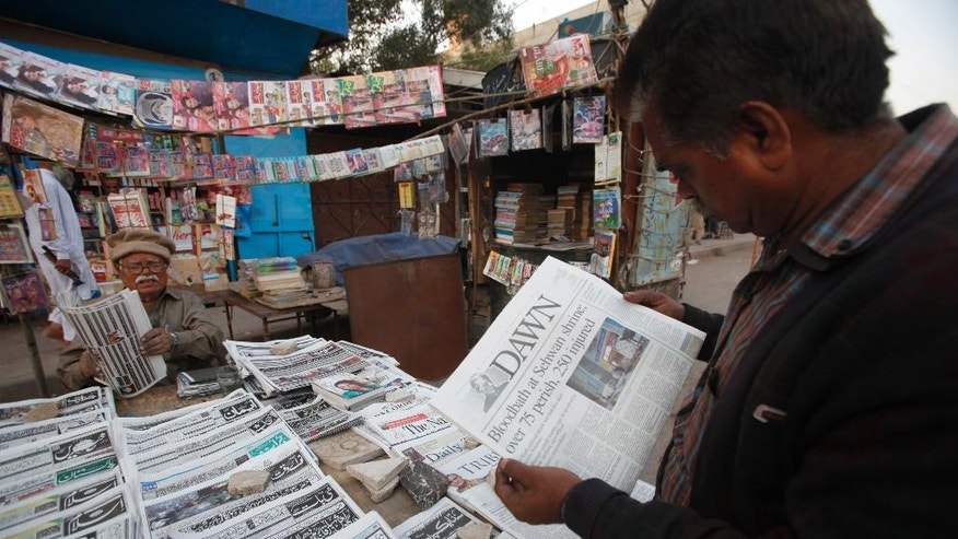 A man reads a newspaper carrying headlines about Thursday's suicide bombing at the Lal Shahbaz Qalandar shrine, in Karachi, Pakistan, Friday, Feb. 17, 2017. Pakistani security forces arrested dozens of suspects in sweeping raids a day after the massive bombing claimed by the Islamic State group killed dozens of worshippers at the famed Sufi shrine in a southern province. (AP Photo/Fareed Khan)