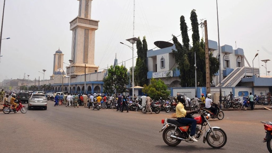 People, rear, gather outside Zogo Mosque for Friday afternoon prayers in Cotonou, Benin, Friday, Feb. 17, 2017. Tensions have mounted in Benin after authorities cleared illegal structures from sidewalks including temporary awnings beside mosques where large numbers of worshippers gather for Friday prayers. (AP Photo/Salako Valentin)