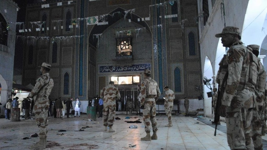 Pakistani para-military soldiers stand alert after a deadly suicide attack at the shrine of famous Sufi Lal Shahbaz Qalandar in Sehwan Pakistan Thursday Feb. 16 2017. An Islamic State suicide bomber targeted worshippers at a famous shrine in southern