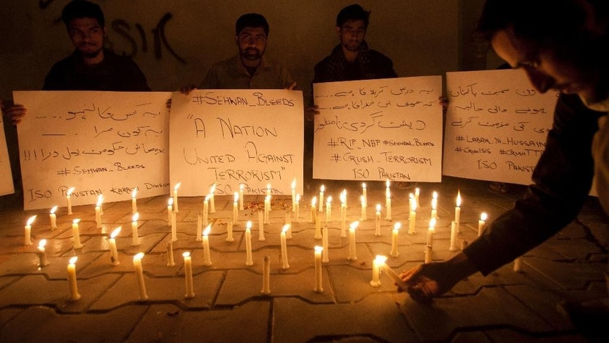 Pakistani students light candles to condemn the recent attack on a shrine in interior Sind province Thursday Feb. 16 2017 in Karachi Pakistan. An Islamic State suicide bomber targeted worshippers at a famous shrine in southern Pakistan on Thursday