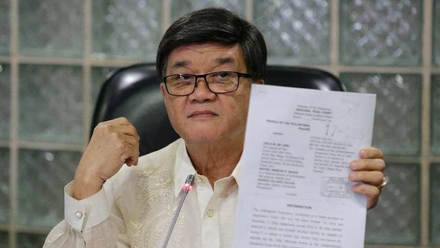 Philippine Justice Secretary Vitaliano Aguirre II displays a document showing criminal charges that were filed against opposition Sen. Leila de Lima during a press conference in Manila, Philippines, Friday, Feb. 17, 2017. Aguirre said state prosecutors filed three charges against Sen. Leila de Lima for allegedly receiving money from detained drug lords in a move that can lead to the arrest of one of the president's most vocal critics. (AP Photo/Aaron Favila)