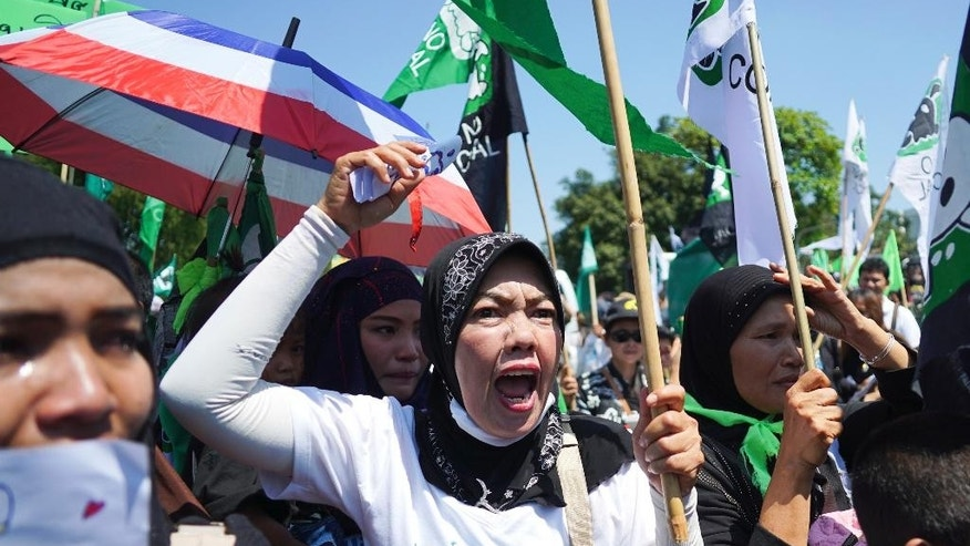 Suda Hemsanga, a Krabi resident, yells in protest against a proposed coal-fired plant on Thailand's coast, in Bangkok, Thailand, Feb. 17, 2017. Thai government's committee approved construction of an 800-megawatt coal power plant near pristine beaches on the Andaman Sea, Prime Minister Prayuth Chan-ocha announced Friday. The plant and an accompanying dock are slated to be built next to an existing oil plant on the coast in Krabi, a major tourist destination. (AP Photo/Dake Kang)