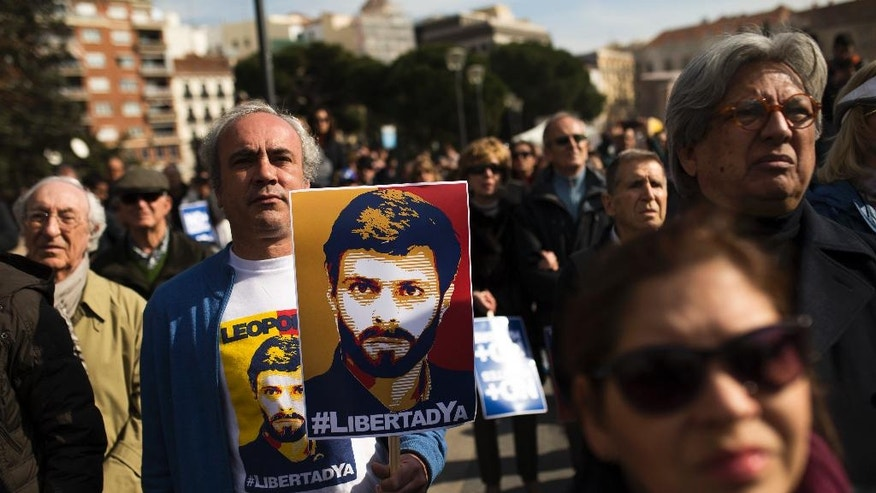 "A protestor holds a poster with the image of Venezuela's jailed opposition leader Leopoldo Lopez, listens to speeches with others during a protest to demand the release of Lopez and other jailed opposition leaders, in Madrid, Saturday, Feb. 18, 2017. The poster reads in Spanish: ""Freedom Now"". (AP Photo/Francisco Seco)"