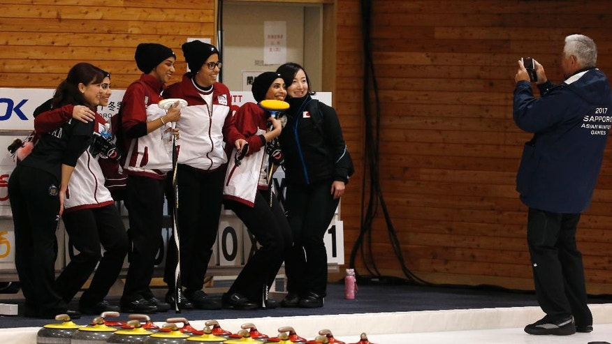Qatar's players in white and red, pose for a photo with Japanese players, in black, after their loss during a round-robin Curling game at the Asian Winter Games in Sapporo, northern Japan, Saturday, Feb. 18, 2017. (AP Photo/Shuji Kajiyama)