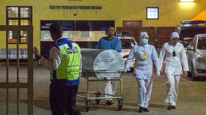 Medical staff carry a metallic bed which is used for transporting dead bodies out of the forensic department at Kuala Lumpur Hospital in Kuala Lumpur, Malaysia, Sunday, Feb. 19, 2017. Speculation that the estranged half brother of the North Korean leader was killed by two young female agents at the busy Kuala Lumpur airport last week left even the most seasoned toxicology sleuths shaking their heads. (AP Photo/Alexandra Radu)