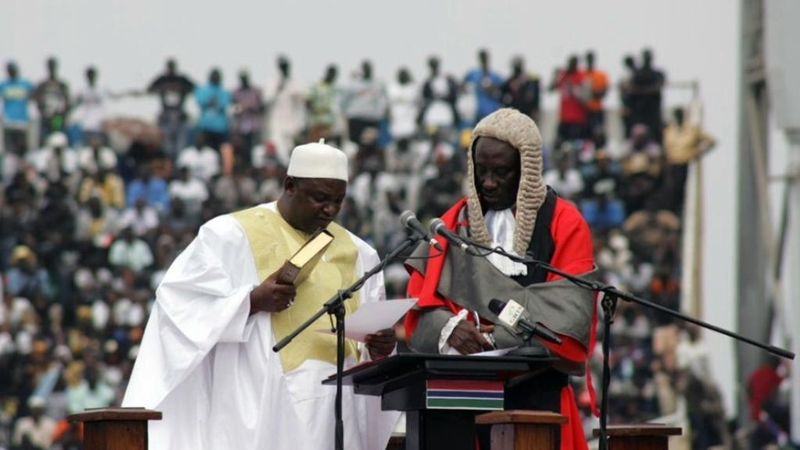 Gambia President Adama Barrow, left, reads, during his inauguration ceremony in Banjul , Gambia, Saturday, Feb. 18, 2017. Gambia's new president thanked his nation and promised greater freedom, an improved economy and better education as thousands attended a ceremony Saturday marking his inauguration after a tense political standoff with the country's former longtime leader. (AP Photo/ Kuku Marong)