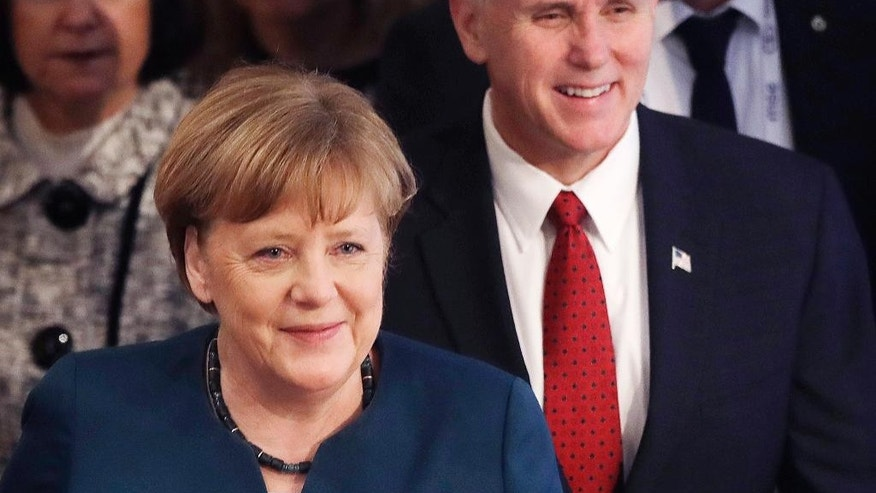 German Chancellor Angela Merkel, left, and United States Vice President Mike Pence arrive at the Munich Security Conference in Munich, Germany, Saturday, Feb. 18, 2017. The annual weekend gathering is known for providing an open and informal platform to meet in close quarters. (AP Photo/Matthias Schrader)
