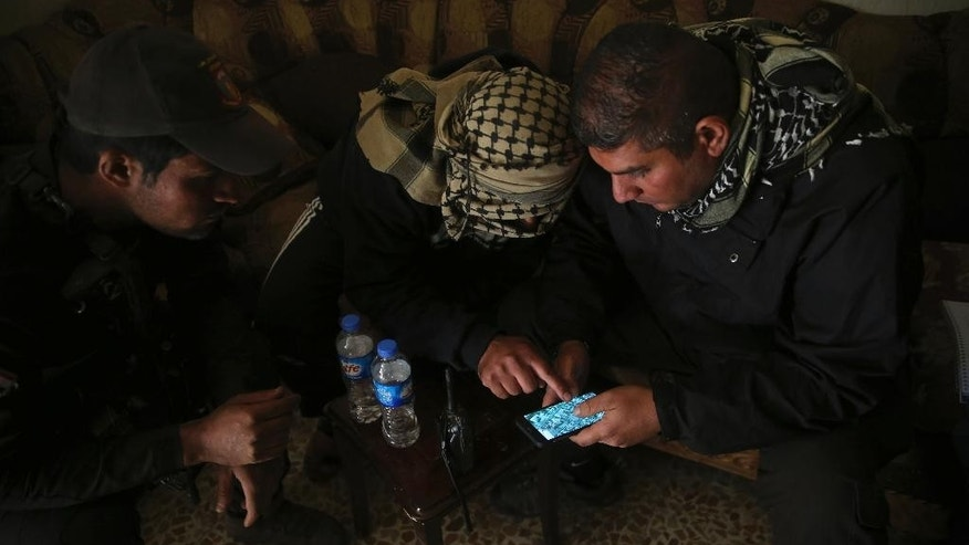 FILE - In this Nov. 25, 2016 photo, Special forces Lt. Col. Ali Hussein, right, listens to an Iraqi informant, center, giving information about Islamic State militant positions on a mobile map, in the Bakr front line neighborhood, in Mosul, Iraq. More than 300 people inside Mosul have worked as informants for Iraqi intelligence, passing on information about Islamic State militants, a major boost in the battle to retake the city. (AP Photo/Hussein Malla, File)