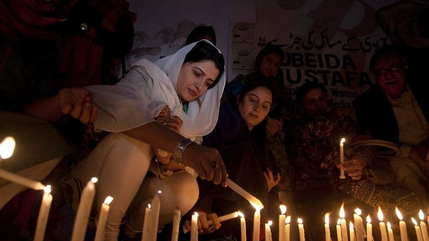 Pakistani women light candles to pay tribute to the victims of Thursday's suicide attack at a shrine, in Karachi, Pakistan, Friday, Feb. 17, 2017. A brutal attack on a beloved Sufi shrine that killed dozens of people raised fears that the Islamic State group has become emboldened in Pakistan, aided by an army of homegrown militants benefiting from hideouts in neighboring Afghanistan, analysts and officials said Friday. (AP Photo/Shakil Adil)