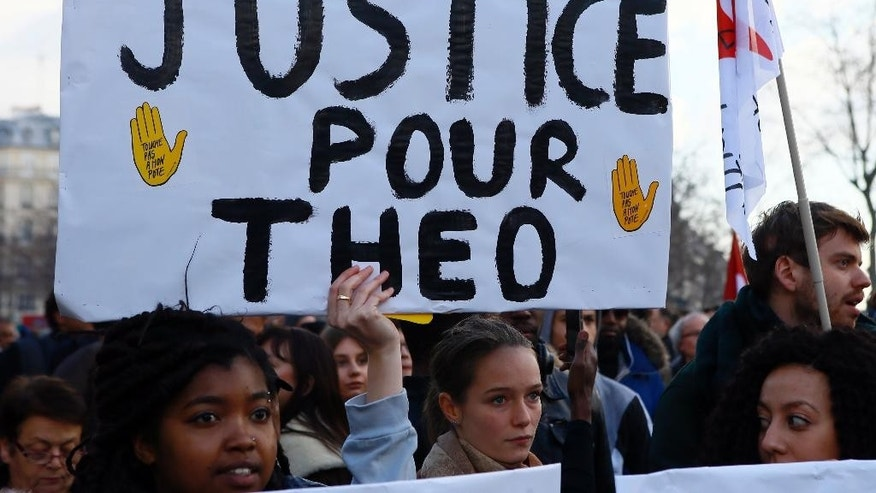 "Demontrators hold a placard reading ""Justice for Theo"" during a protest against alleged police abuse, in Paris Saturday, Feb. 18, 2017. Anti-racism groups and other activists are gathered in Paris in support of victims of police violence, after a young black man was allegedly raped with a police baton in an incident that prompted violent protests in impoverished suburbs. (AP Photo/Francois Mori)"