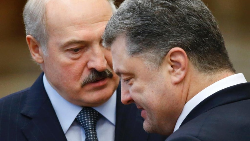 FILE - In this Thursday, Feb. 12, 2015 file photo Ukrainian President Petro Poroshenko, right, speaks with Belarusian President Alexander Lukashenko after the peace talks in Minsk, Belarus. In more than two decades in power, the autocratic leader of Belarus has cast his nation as Moscow's closest ally, securing tens of billions of dollars in Russian subsidies. Now, the Kremlin finally seems to have lost patience with its unruly ally. (AP Photo/Sergei Grits, file)