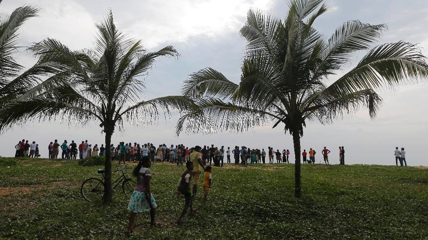 Sri Lankan's watch the rescue operation from the shore after a boat capsized off the country's southwestern coast in Beruwala, 60 kilometers (37 miles) south of Colombo, Sri Lanka, Sunday, Feb. 19, 2017. (AP Photo/Eranga Jayawardena)