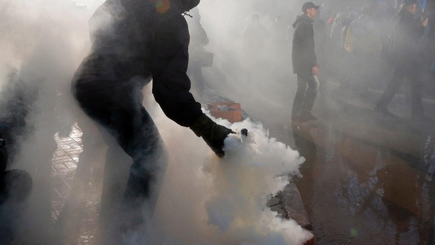 An activist throws a smoke grenade toward riot police during a protest rally in front of the President Office in Kiev, Ukraine, Sunday, Feb. 19, 2017. Protesters were demanding a stop to trade relations with Russia-occupied Ukrainian territories. (AP Photo/Efrem Lukatsky)