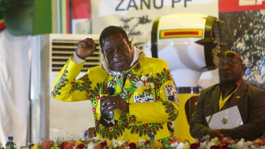 In this photo taken Dec. 17, 2016, Zimbabwean Deputy President Emmerson Mnanangagwa chants the party slogan at a Zanu PF conference in Masvingo, Zimbabwe. Mnangagwa is a key figure in the succession talk and an associate of Mugabe dating back to the guerilla war against minority rule in what was then Rhodesia. As the world's oldest head of state approaches his 93rd birthday on Tuesday Feb. 21, 2017. Zimbabwe has been planning a party for thousands of people. (AP Photo/Tsvangirayi Mukwazhi)