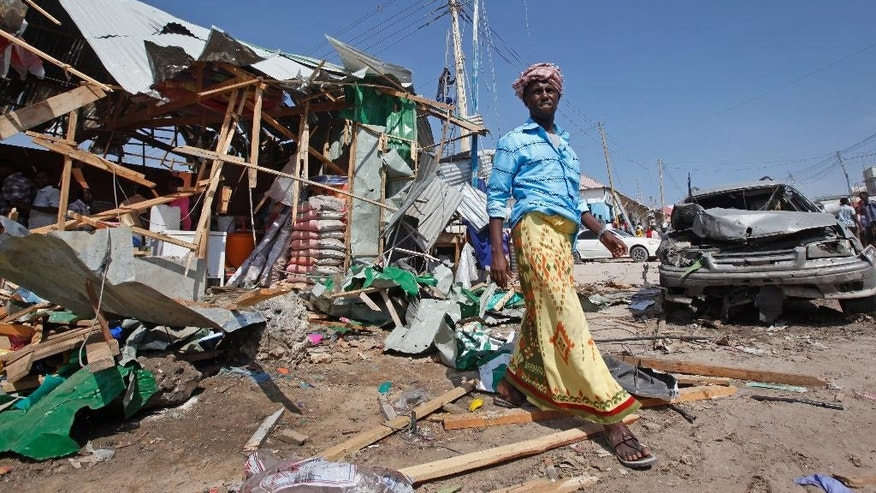 A man walks past the wreckage of shops destroyed by a blast in a market in the capital Mogadishu, Somalia, Sunday, Feb. 19, 2017. A Somali police officer says a blast at a busy market in the western part of Somalia's capital tore through shops and food stands and killed more than a dozen people and wounded many others. (AP Photo/Farah Abdi Warsameh)