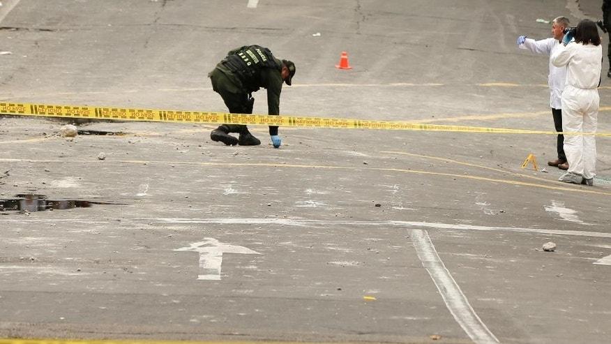 Police and investigators inspect the site where a homemade bomb exploded near the Santamaria bull ring in Bogota, Colombia, Sunday, Feb. 19, 2017. The artefact was detonated just a few hours before a scheduled bullfight, killing a police officer and injuring several dozen bystanders. (AP Photo/Ricardo Mazalan)