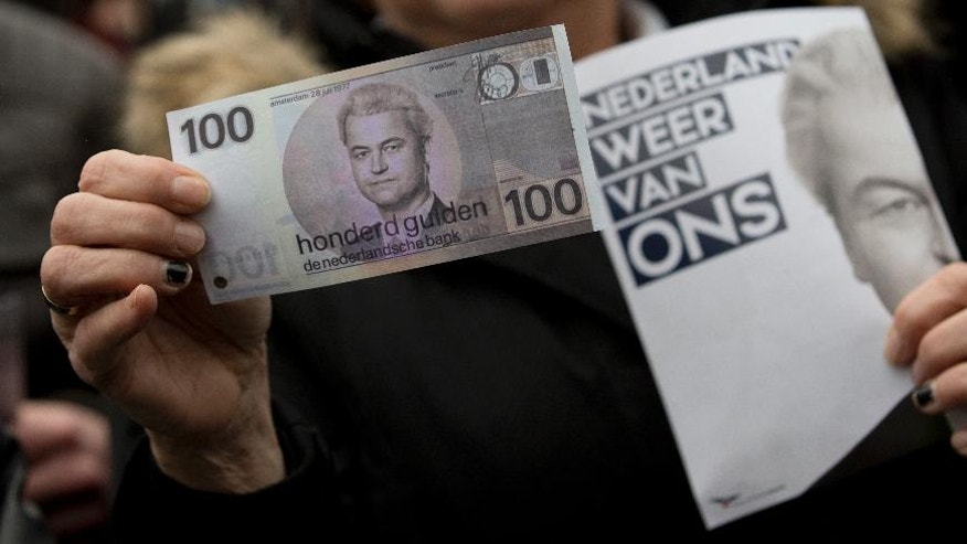"A woman holds a fake hundred guilder note, the Dutch currency before the introduction of the Euro, bearing the portrait of firebrand int-islam lawmaker Geert Wilders and a flyer reading ""Netherlands Ours Again"" during his election campaign stop in Spijkenisse, near Rotterdam, Netherlands Saturday Feb. 18, 2017. Now, as a March 15 parliamentary election looms, the political mood is turning inward as Wilders dominates polls with an isolationist manifesto that calls for the Netherlands ""to be independent again. So out of the EU."" (AP Photo/Peter Dejong)"