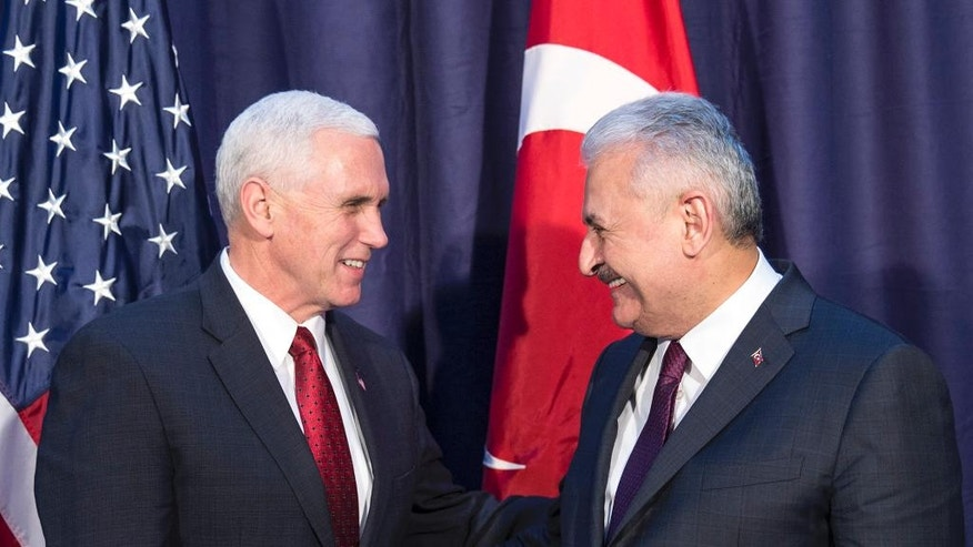 "United States Vice President Mike Pence, left and Turkey's Prime Minister Binali Yildirim, talk prior to their meeting during the Munich Security Conference in Munich, Germany, Saturday, Feb. 18, 2017.  America's commitment to NATO is ""unwavering,"" Pence said Saturday, reassuring allies about the direction the Trump administration might take but leaving open questions about where Washington saw its relationship with the European Union and other international organizations.  (Prime Minister's Press Service, Pool Photo via AP)"