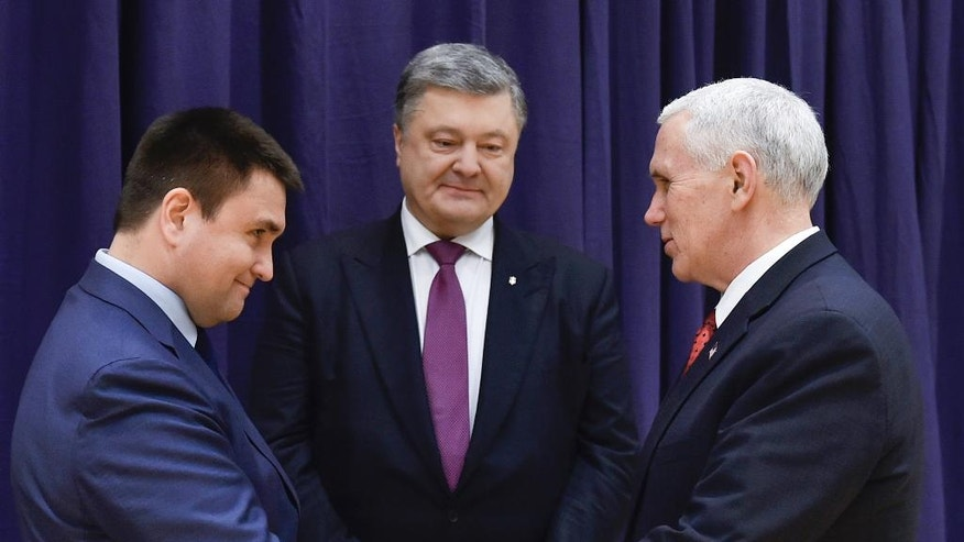 "United States Vice President Mike Pence, right, shakes hands with Ukrainian Foreign Minister Pavlo Klimkin, left, as Ukraine's President Petro Poroshenko looks on, centre, during the Munich Security Conference in Munich, Germany, Saturday, Feb. 18, 2017.  America's commitment to NATO is ""unwavering,"" Pence said Saturday, reassuring allies about the direction the Trump administration might take but leaving open questions about where Washington saw its relationship with the European Union and other international organizations.  (Mykola Lazarenko/Presidential Press Service Pool Photo via AP)"