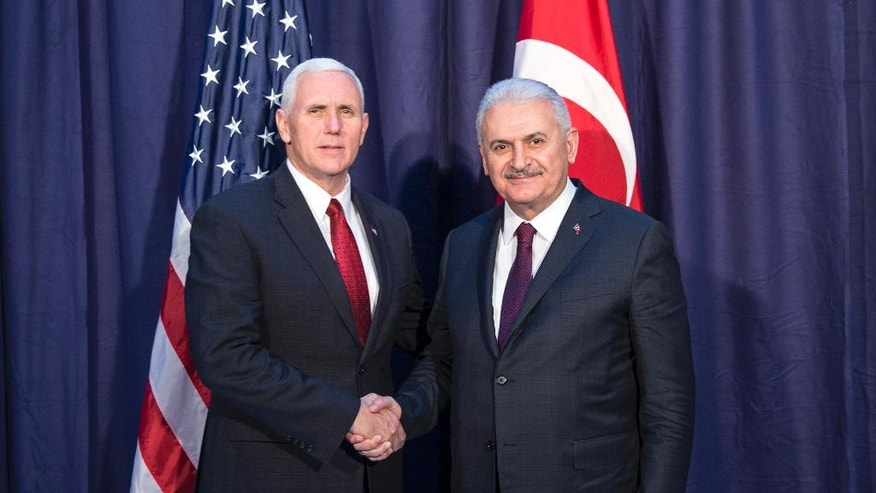 "United States Vice President Mike Pence, left and Turkey's Prime Minister Binali Yildirim, right, shake hands for the photographers prior to their meeting during the Munich Security Conference in Munich, Germany, Saturday, Feb. 18, 2017.  America's commitment to NATO is ""unwavering,"" Pence said Saturday, reassuring allies about the direction the Trump administration might take but leaving open questions about where Washington saw its relationship with the European Union and other international organizations. (Prime Minister's Press Service, Pool Photo via AP)"