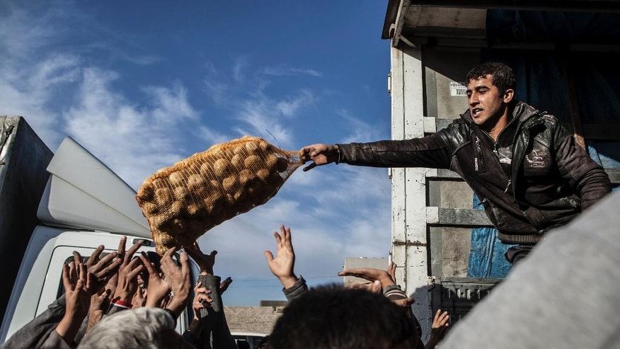 In this Dec. 4, 2016 file photo, an Iraqi man distributes potatoes to civilians in the Samah district of Mosul, Iraq. (AP Photo/Manu Brabo, File)