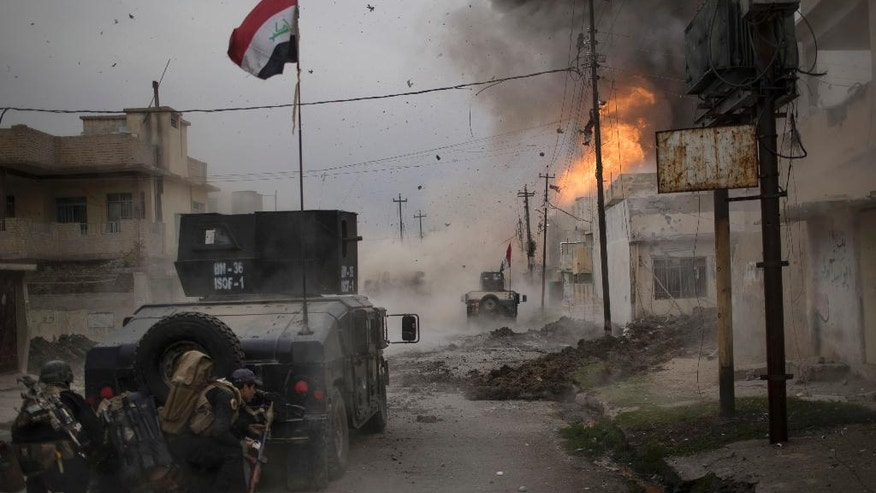 FILE -- In this Nov. 16, 2016 file photo, a car bomb explodes next to Iraqi special forces armored vehicles as they advance towards Islamic State held territory in Mosul, Iraq. Troops have established a foothold in the city's east from where they are driving northward into the Tahrir neighborhood. The families in Tahrir are leaving their homes to flee the fighting. (AP Photo/Felipe Dana, File)
