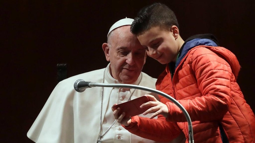 A boy shows his phone to Pope Francis during a visit to the parish of Santa Maria Josefa del Cuore di Gesu', in Rome, Sunday, Feb. 19, 2017. (AP Photo/Alessandra Tarantino)