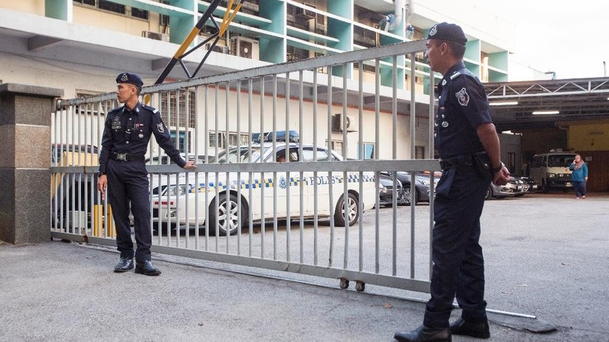 Malaysian police officers guard the gate of the forensic department at Kuala Lumpur Hospital in Kuala Lumpur, Malaysia, Monday, Feb. 20, 2017. Investigators are looking for four North Korean men who flew out of Malaysia the same day Kim Jong Nam, the North Korean ruler's outcast half brother, apparently was poisoned at an airport in Kuala Lumpur, Malaysian police said Sunday. Since Kim's death last week, authorities have been trying to piece together details of what appeared to be an assassination. (AP Photo/Alexandra Radu)