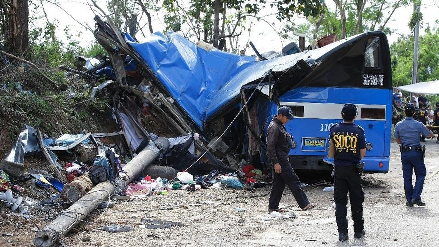 Police investigators stand beside the wreckage of a bus that crashed on a downhill road in Tanay, Rizal province, east of Manila, Philippines, Monday, Feb. 20, 2017. More than a dozen mostly college students on a camping trip were killed when their rented bus lost its brakes on the downhill road slammed into a post, town officials said. (AP Photo/Aaron Favila)