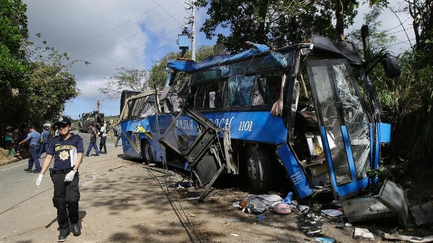 A police investigator passes by the wreckage of a bus that crashed on a downhill road in Tanay, Rizal province, east of Manila, Philippines, Monday, Feb. 20, 2017. More than a dozen mostly college students on a camping trip were killed when their rented bus lost its brakes on the downhill road slammed into a post. (AP Photo/Aaron Favila)