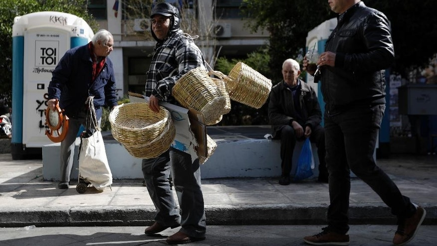 A street vendor carries baskets as other pedestrians walk at a market area in Athens, Monday, Feb. 20, 2017. Greece remains dependent on bailout loans from its partners in the eurozone to pay its debts and protect it from bankruptcy and a potential exit from the euro. (AP Photo/Thanassis Stavrakis)