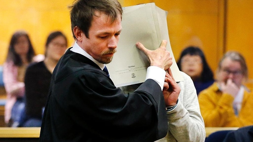 A 16-year-old South Korean covers his face as he is led into a court room by a lawyer  in Frankfurt, Germany, Monday, Feb. 20, 2017. He is the main suspect accused of murder following the death a 41-year-old woman in an apparent exorcism ritual in a room in a Frankfurt hotel. (AP Photo/Michael Probst)