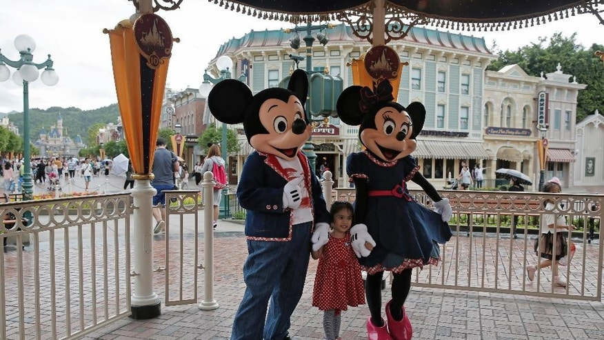 FILE - In this  June 10, 2016, file photo, a girl poses with Mickey and Minnie Mouse at the Hong Kong Disneyland. Hong Kong Disneyland posted a wider annual loss on Monda, Feb. 20, 2017 as attendance by mainland Chinese tourists dropped amid a softer tourism market. The park said it lost 171 million Hong Kong dollars ($22 million) on revenue of HK$4.8 billion for its most recent financial year, which ended Oct. 3. (AP Photo/Kin Cheung, File)