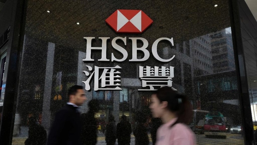 "People walk past a branch of HSBC bank in Hong Kong, Tuesday, Feb. 21, 2017. London-based bank HSBC reported Tuesday that annual profit slumped following a year it said would be remembered for ""unexpected economic and political events"" and warned of risks in 2017 to the global economy's continuing recovery. (AP Photo/Vincent Yu)"