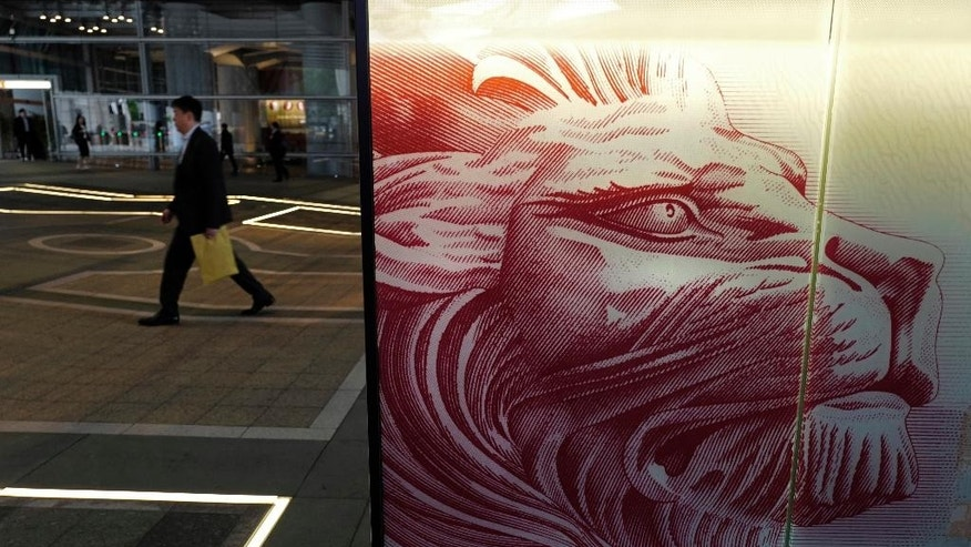 "A man walks past the HSBC's Hong Kong headquarters in Hong Kong, Tuesday, Feb. 21, 2017. London-based bank HSBC reported Tuesday that annual profit slumped following a year it said would be remembered for ""unexpected economic and political events"" and warned of risks in 2017 to the global economy's continuing recovery. (AP Photo/Vincent Yu)"