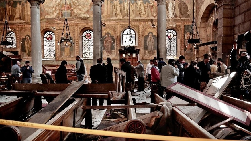 "FILE -- In this Dec. 11, 2016 file photo, security forces examine the scene inside the St. Mark Cathedral in central Cairo, following a bombing that killed dozens of people. A 20-minute video from an Islamic State affiliate in Egypt, which emerged Monday, Feb. 20, 2017, showed the suicide bomber who attacked the church and vowed more attacks on the country's Christian minority. The video said Christians are the extremist group's ""favorite prey."" (AP Photo/Nariman El-Mofty, File)"